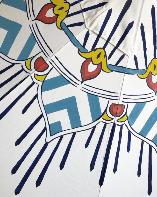 detail of an elegant blue and white patio umbrella by pearl and maude