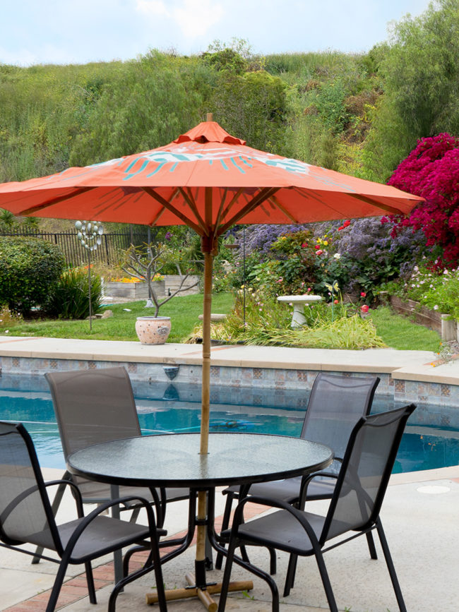 colorful custom patio umbrella painted by Teale Hatheway of pearl and maude - beautiful poolside space with orange umbrella