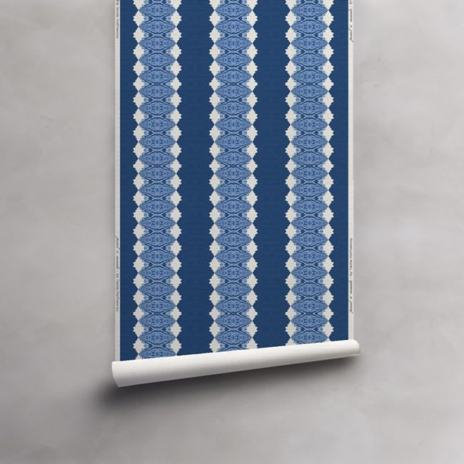 Roll of deep blues and white wallpaper on grasscloth wallcovering. Design - Lou by Pearl and Maude