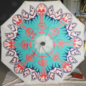 a hand painted patio umbrella in the process of being painted