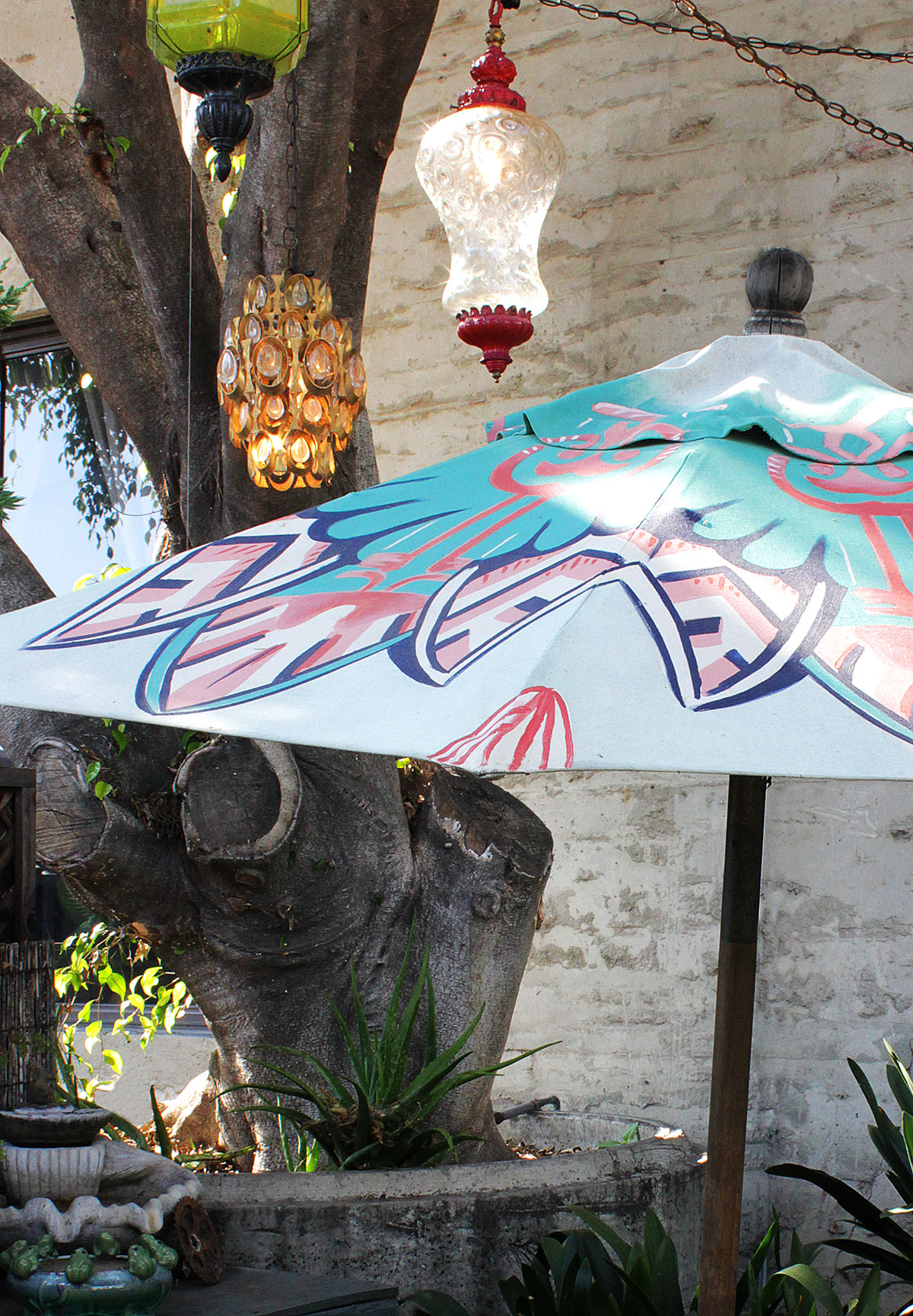 turquoise and coral hand painted patio umbrella in the garden with trees and hanging lanterns