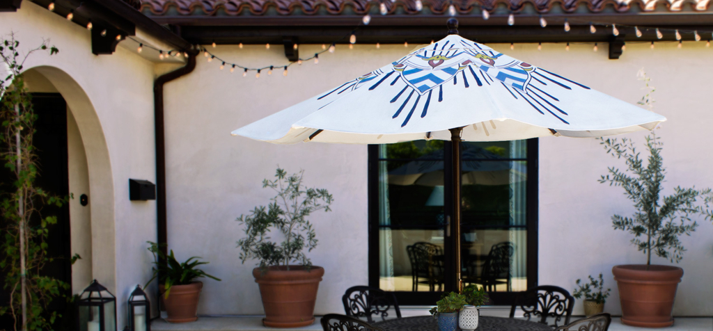 beautiful blue and white custom patio umbrella in a Spanish style courtyard by pearl and maude
