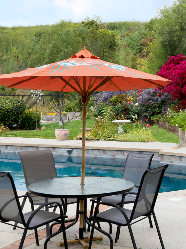 custom hand painted patio umbrella in orange white and turquoise by Pearl and Maude
