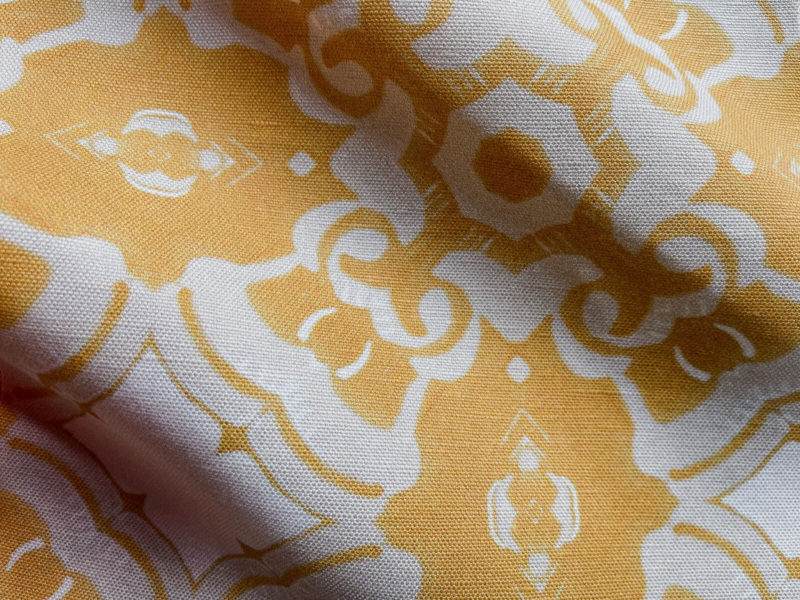 A fabric swatch of Pearl & Maude's medallion pattern Alexandria in daisy yellow, cream and white