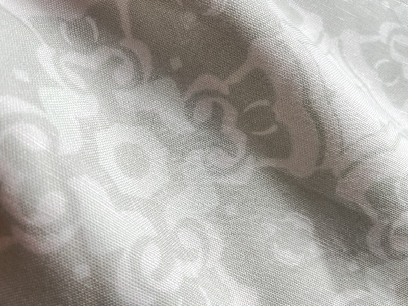 A fabric swatch of Pearl & Maude's medallion pattern Alexandria in sea neutral cream and white