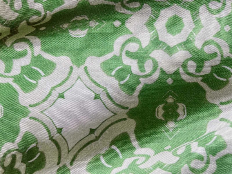 A fabric swatch of Pearl & Maude's medallion pattern Alexandria in moss green, cream and white