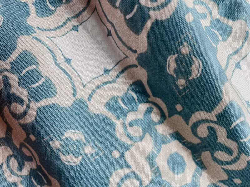 A fabric swatch of Pearl & Maude's medallion pattern Alexandria in sea blue, cream and white