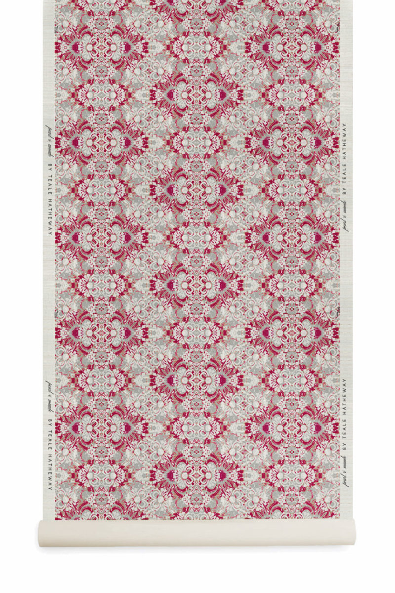A roll of Pearl & Maude's abstract floral Carmen grasscloth wallcovering in berry pink and grey