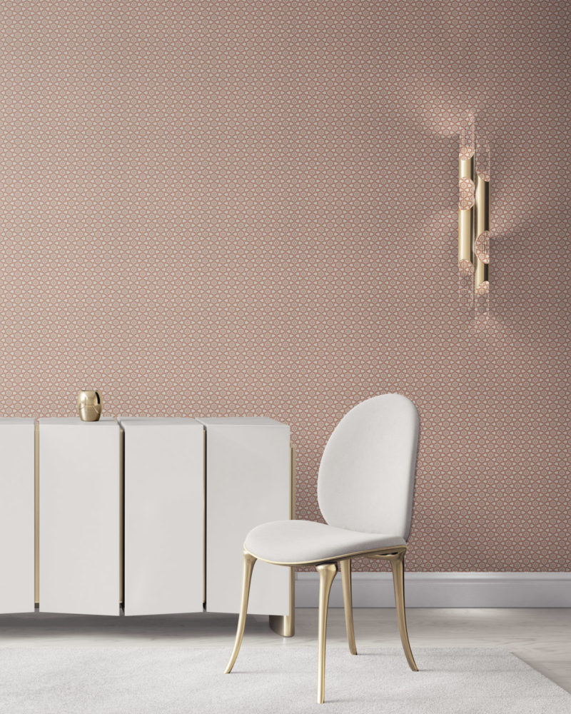 Pearl & Maude's small hexagonal Cora grasscloth wallcovering in clay pink installed in a beautiful living room with white and brass furniture.