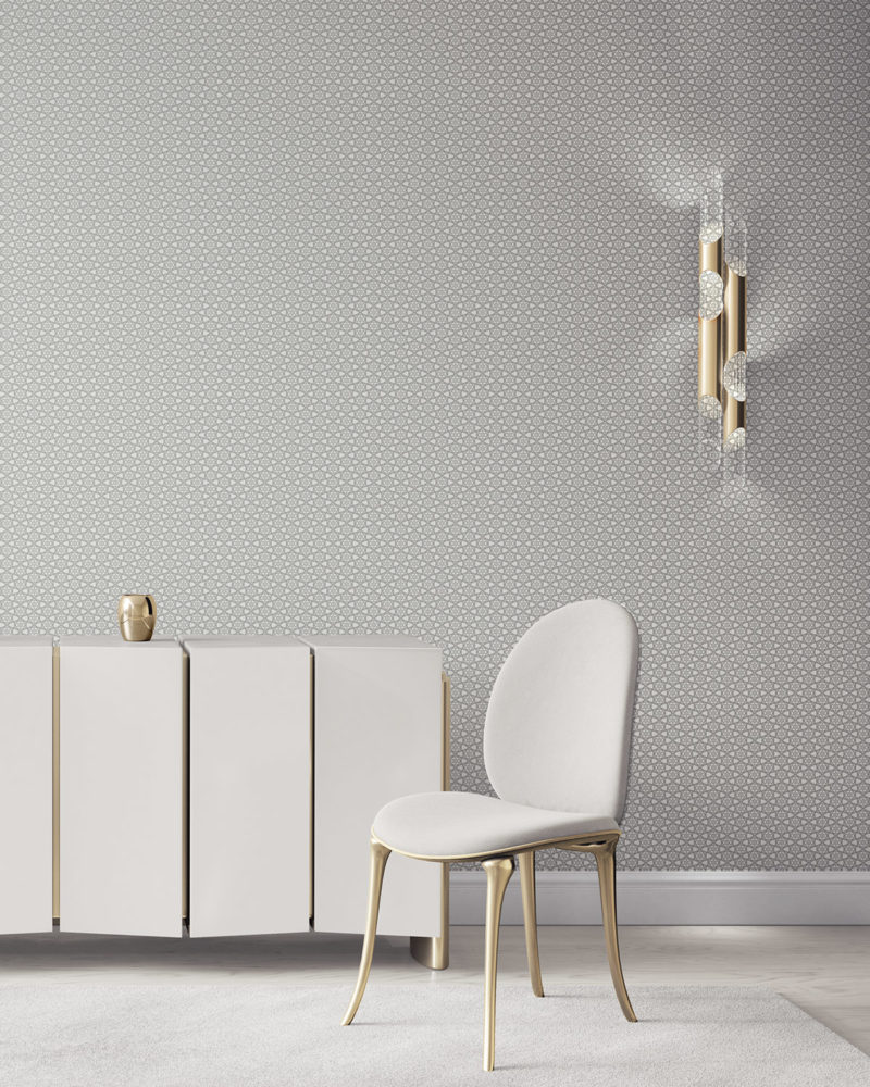 Pearl & Maude's small hexagon Cora nonwoven vellum wallpaper in grey and white installed in a beautiful living room with white and brass furniture.