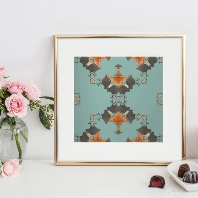 Eva is a square, blue and grey art print. The design was inspired by Art Deco architecture. Here, Eva is seen framed, with flowers and chocolate truffles.